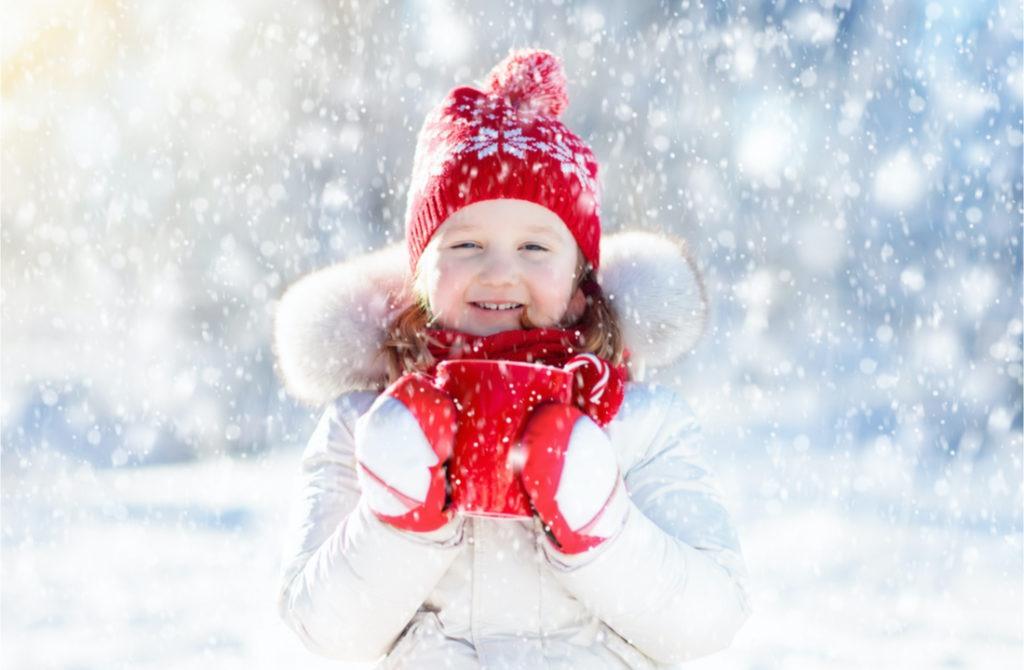 Kind im Schnee trinkt heißen Kakao
